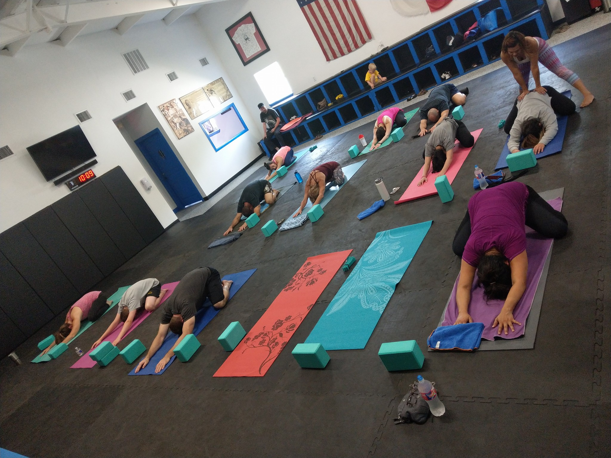 Yoga participants stretching out on mats in the gym